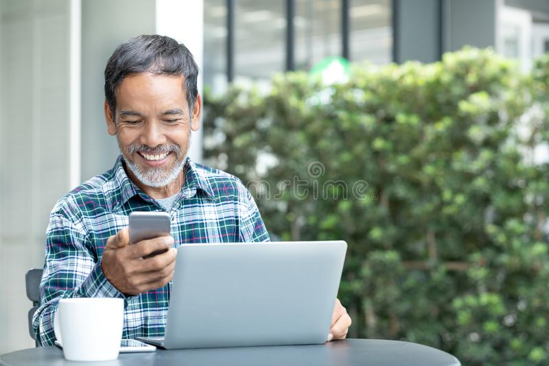 Smiling happy mature man with white stylish short beard using smartphone gadget serving internet. At coffee shop cafe outdoor. Laughing old man using social stock images