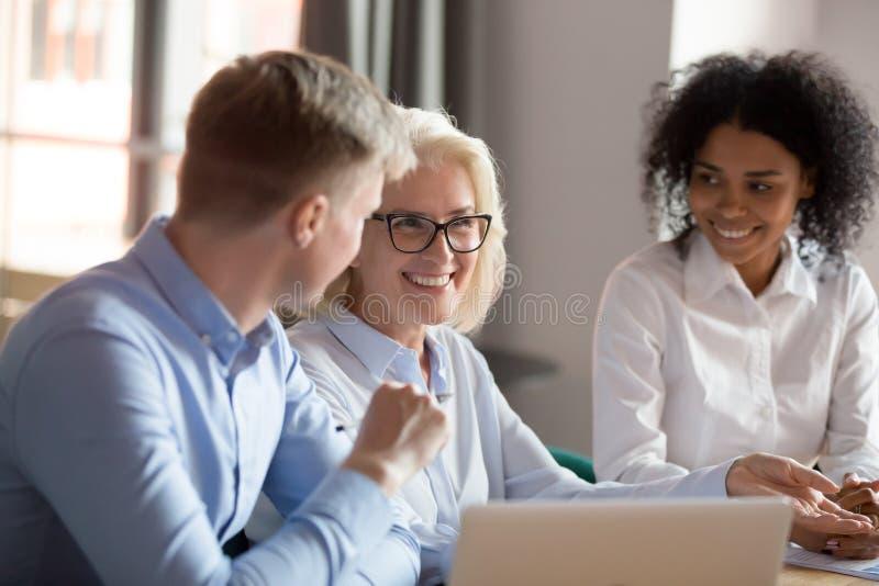Smiling mature female mentor executive talking at diverse group meeting stock image