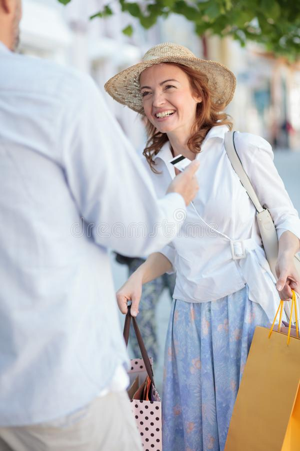 Smiling happy mature woman carrying full shopping bags. Her husband is giving her a credit car stock images