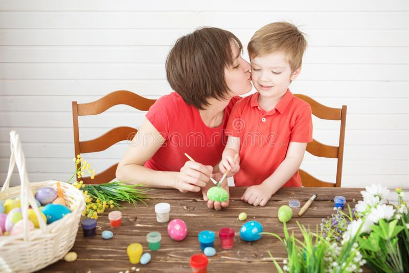 Smiling happy mother and child painting easter eggs. Happy family Mom and children son paint easter eggs with colors. Preparation royalty free stock photography