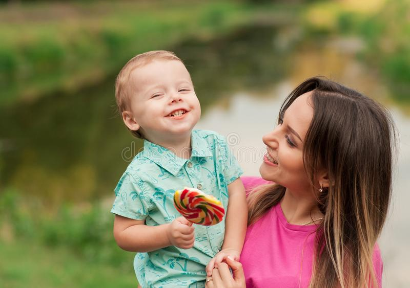 Happy mother holds cute smiling son outdoors stock photography
