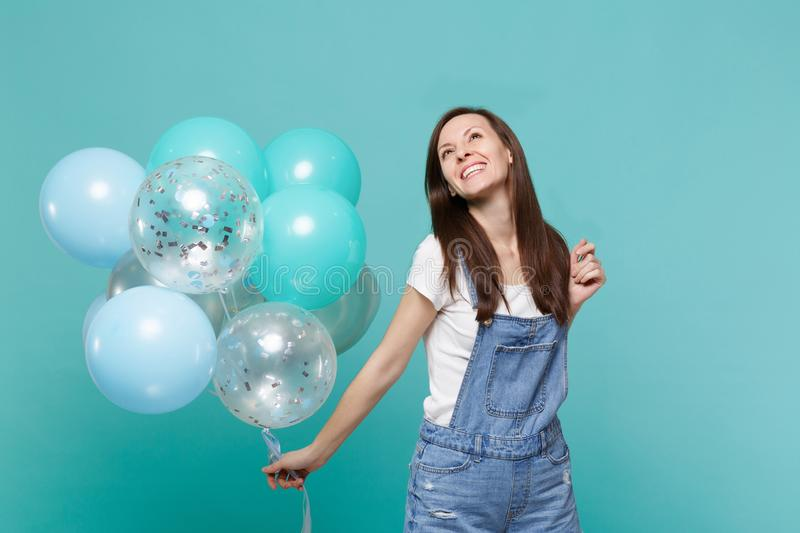 Smiling happy pensive young woman in denim clothes looking up celebrating and holding colorful air balloons isolated on stock images