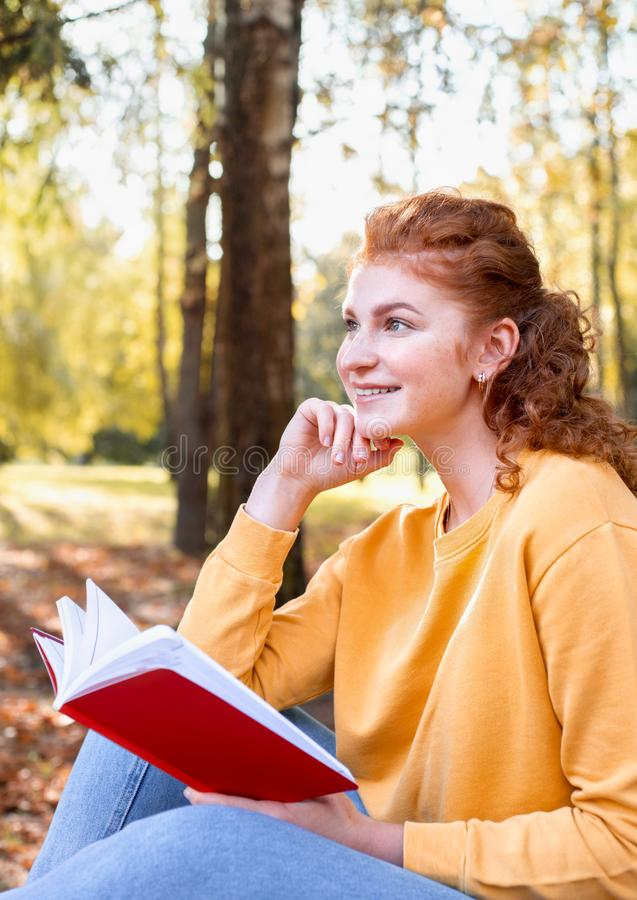 Smiling happy red hair student girl reading a book outside in autumn park stock photography