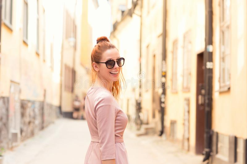 Smiling happy redhead woman looking back while walking on the empty street royalty free stock photos