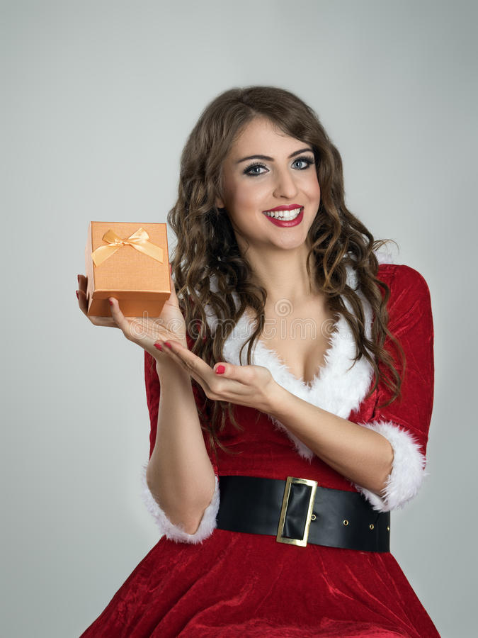 Smiling happy Santa girl showing Christmas present in small golden box with ribbon. Over gray studio background stock photo