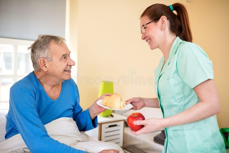 Smiling happy senior patient waiting breakfast at nursing home stock photo