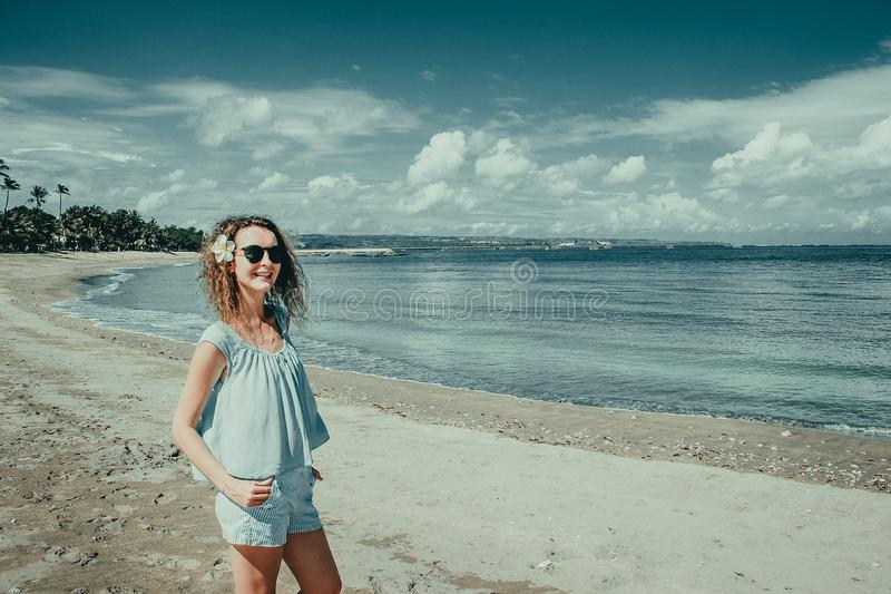 Smiling happy tourist woman enjoy vacation on Kuta beach. Bali traveller. Explore beautiful Indonesia landscape. People travel. Tourism concept. Tropical stock images