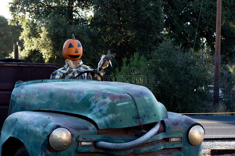 Smiling, happy, welcoming, fun friendly pumpkin head scarecrow driving an old truck to a halloween harvest party. In autumn royalty free stock images