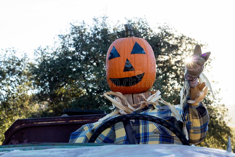 Smiling, happy, welcoming, fun friendly pumpkin head scarecrow driving an old truck to a halloween harvest party. Close-up of smiling, happy, welcoming, fun stock image