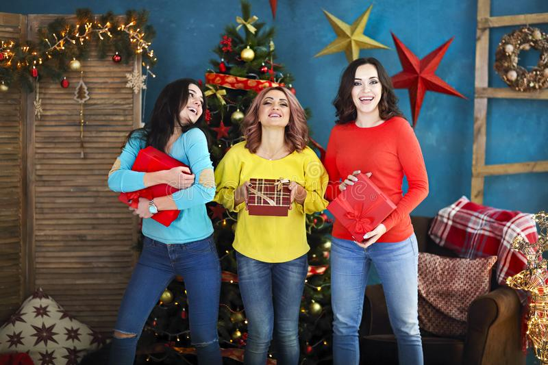Smiling happy woman with gift box over living room on Christmas tree background. Holidays and people concept royalty free stock photography