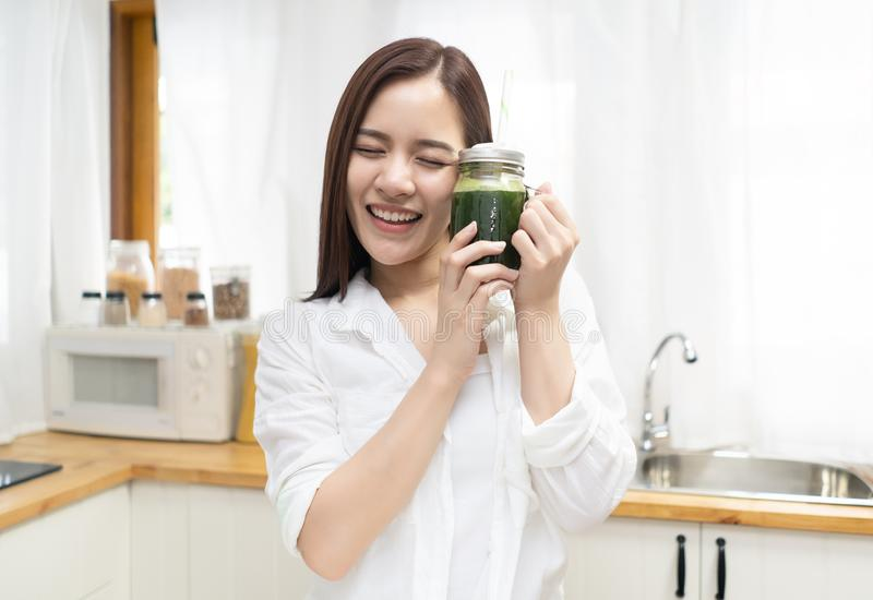 Smiling happy young Asian woman drinking fresh raw green detox vegetable juice at home. Healthy Food Eating, Diet And Lifestyle. Concept. Drinks. Beauty stock photo