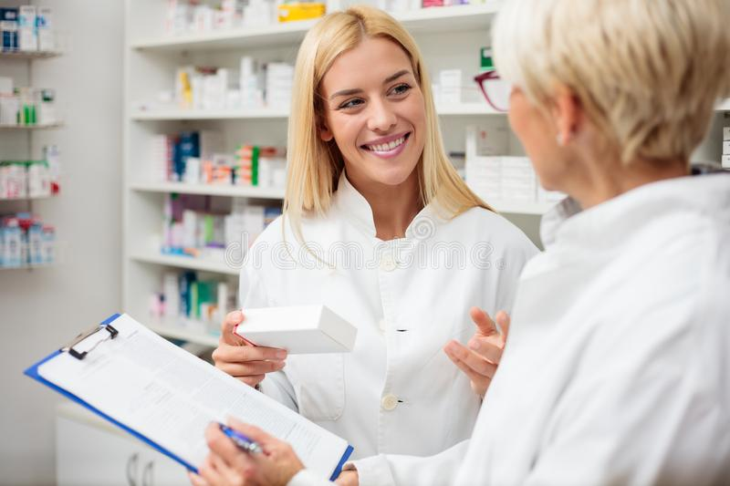 Smiling happy young blond-haired pharmacist holding a box of medications, consulting with her older colleague stock photos
