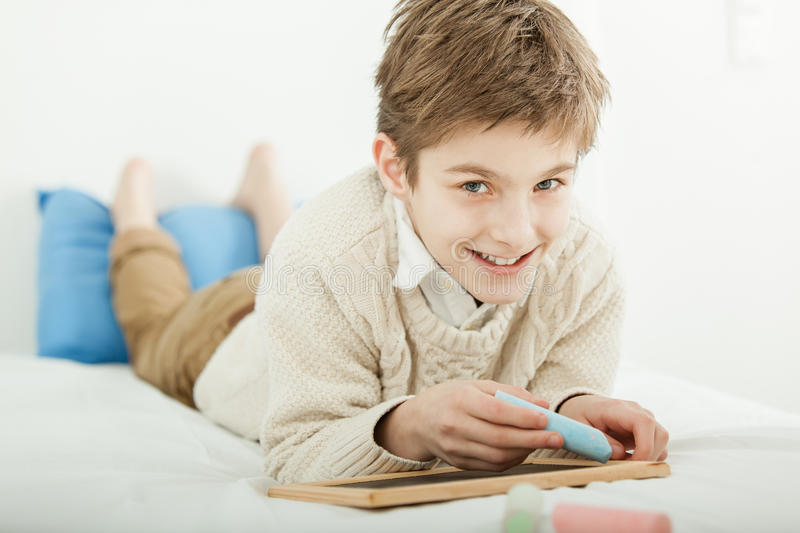 Smiling happy young boy drawing on a slate royalty free stock photo