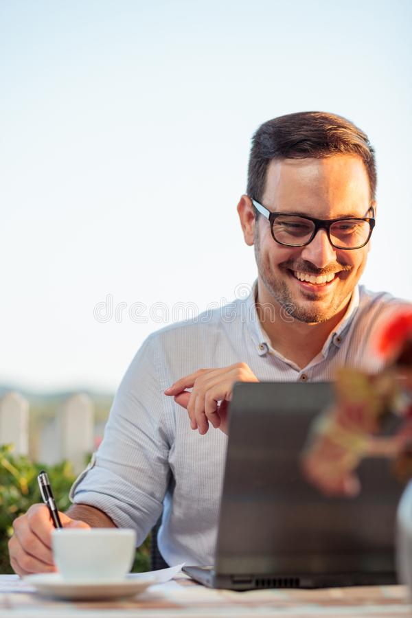 Smiling happy young businessman working in an outdoor restaurant, preparing for important meeting royalty free stock photo