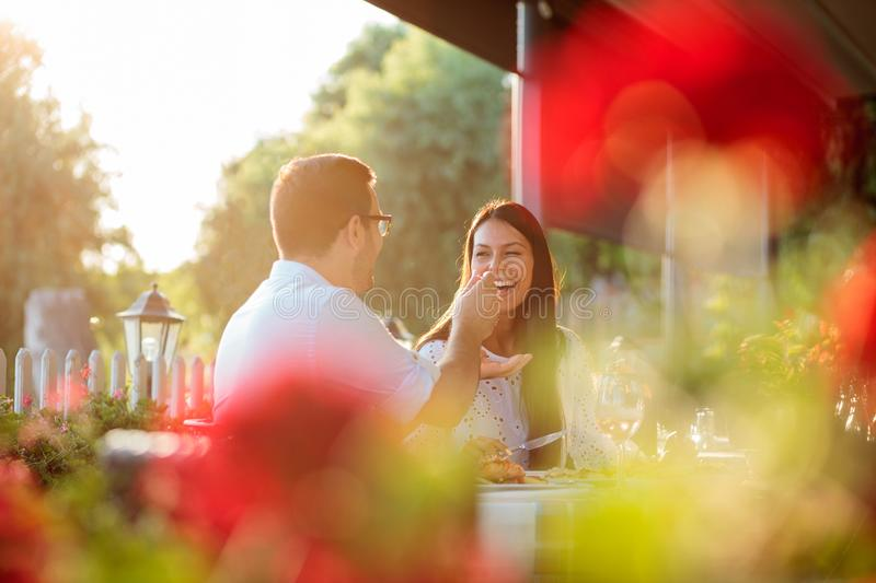Smiling happy young couple enjoying dinner in outdoor restaurant, surrounded by green trees royalty free stock images