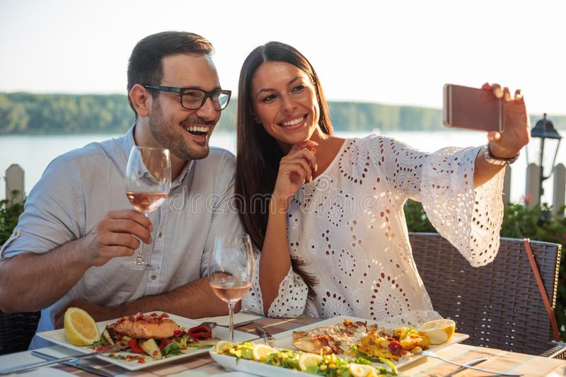 Smiling happy young couple posing for a selfie, eating dinner in a riverside restaurant stock images