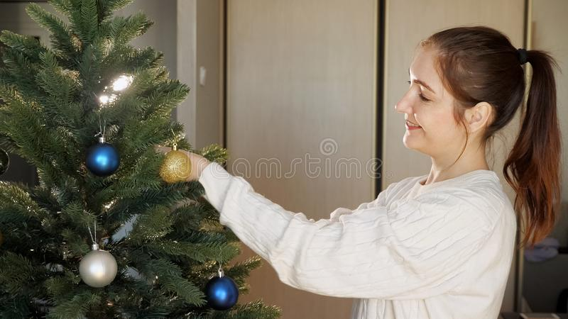 Smiling young lady with ponytail decorates christmas tree royalty free stock photo