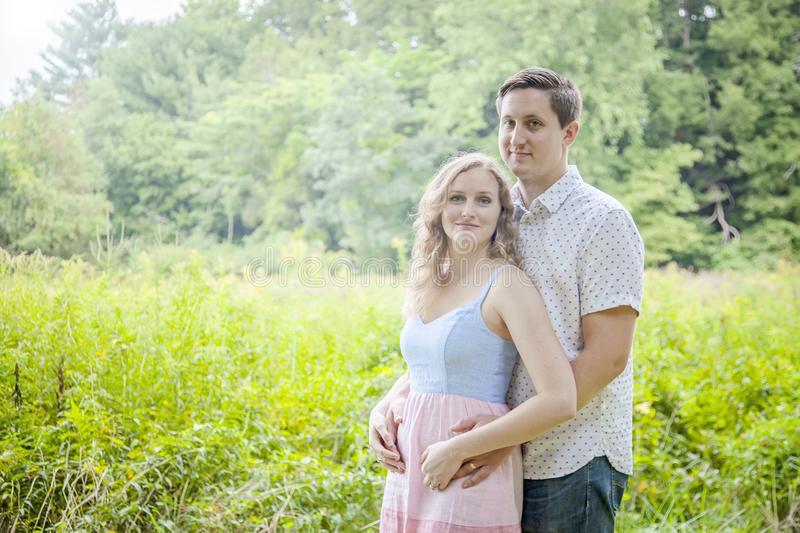 Happy young newly expecting couple portrait outdoors stock photography