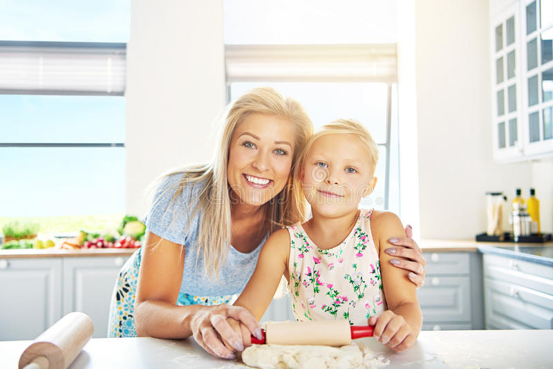 Smiling happy young mother and daughter. Learning to bake posing arm in arm at the kitchen counter stock image