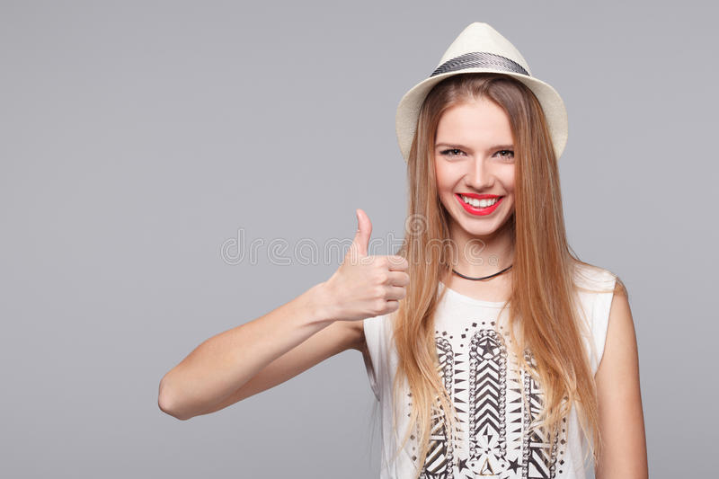 Smiling happy young woman showing thumbs up, isolated on gray stock photo
