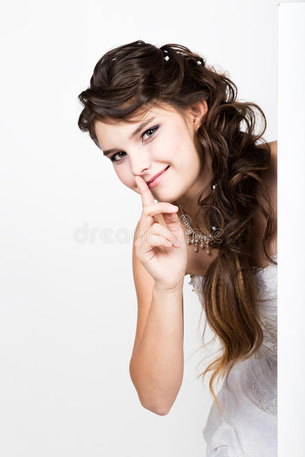 Smiling happy young woman standing behind and leaning on a white blank billboard or placard, expresses different.  royalty free stock photos
