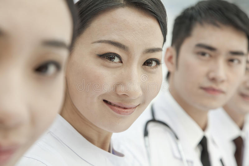 Smiling Healthcare workers standing in a row, China, Close-up on Nurse looking at camera royalty free stock photos