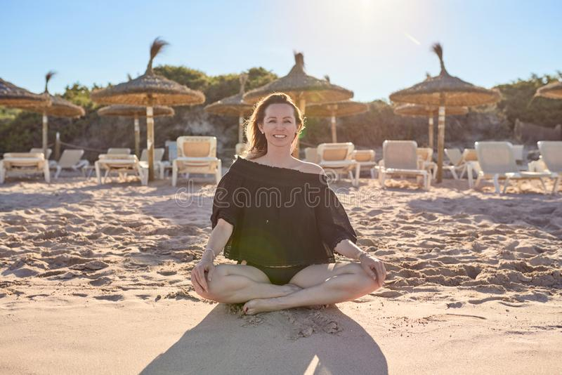 Smiling healthy barefoot woman sitting cross-legged on the beach royalty free stock images