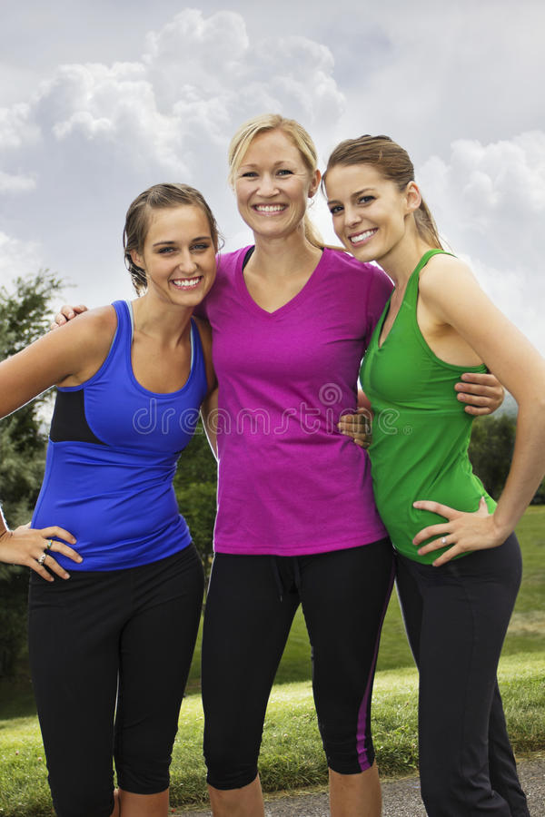 Smiling Healthy Fitness Women. Three healthy beautiful women smiling together before their workout outdoors stock images