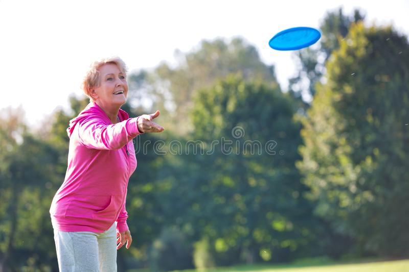 Smiling and healthy senior woman throwing disc in park stock photo