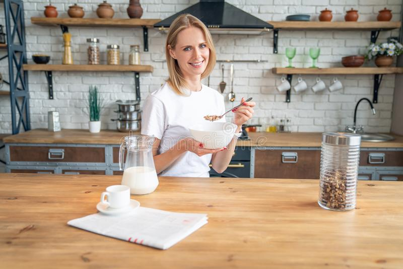Smiling healthy woman eating corn flakes cereal while sitting and having breakfast at the kitchen table royalty free stock image