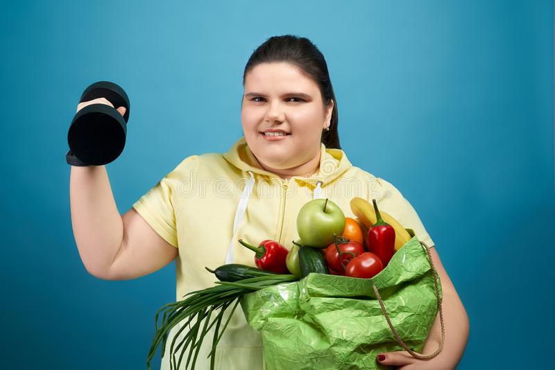 Smiling heavy female keeping fruits, vegetable and dumbbell stock image