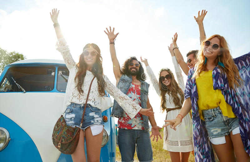 Smiling hippie friends having fun over minivan car royalty free stock photography