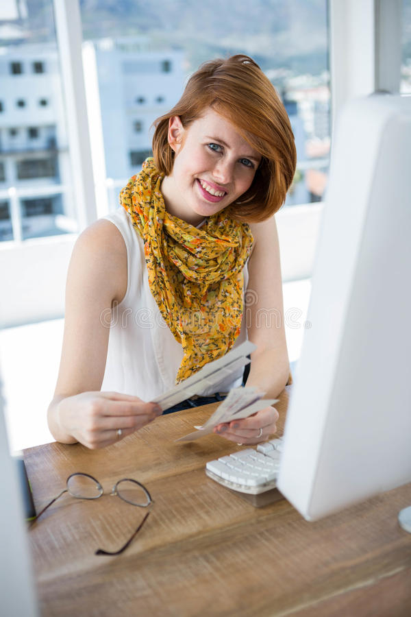 Smiling hipster business woman looking at colour swatches. Smiling hipster business woman, sitting at her desk, looking at colour swatches royalty free stock image