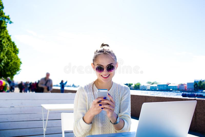 Smiling hipster girl in fashionable glasses skilled blogger posting article in social network via mobile phone stock photography