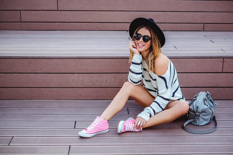 Smiling hipster girl sitting on the stairs royalty free stock photos