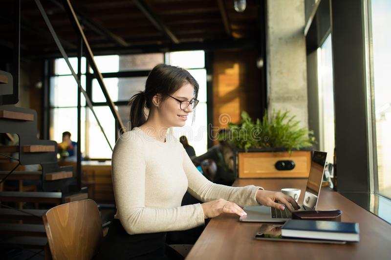Cheerful female blogger reading lifestyle article via notebook gadget royalty free stock photography