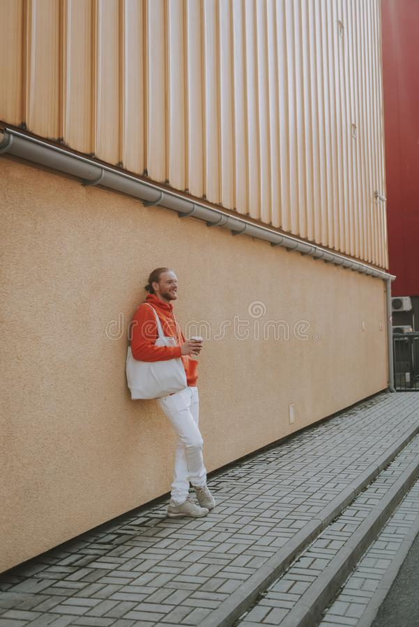 Smiling hipster man drinking coffee on walk. Urban lifestyle concept. Full length side on portrait of young smiling hipster man drinking coffee leaning on stock photo