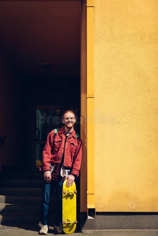 Smiling hipster man staying with yellow skateboard. Urban lifestyle and activity. Full length portrait of young smiling hipster guy with yellow skateboard royalty free stock images
