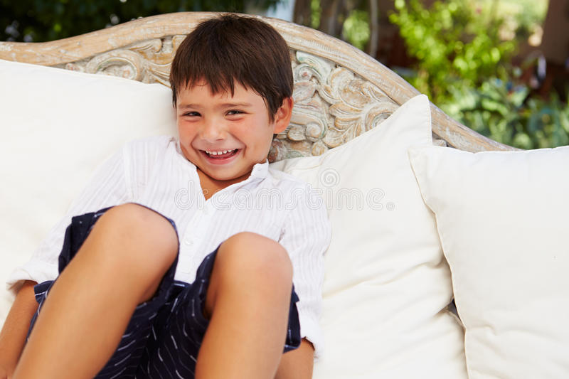 Smiling Hispanic Boy At Home Sitting On Outdoor Seat� stock images