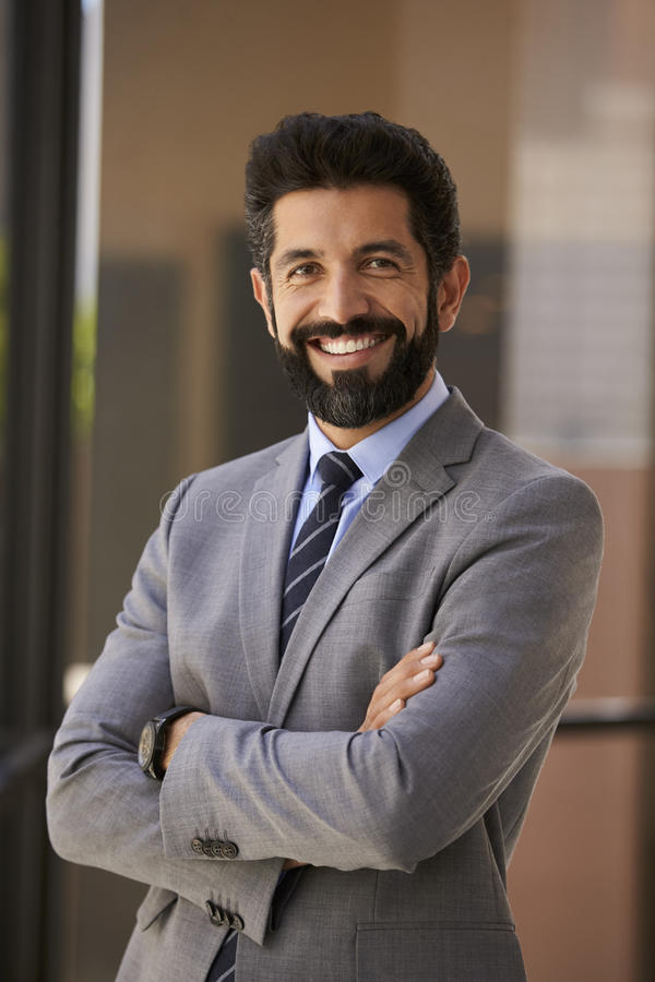 Smiling Hispanic businessman with arms crossed, vertical royalty free stock photos