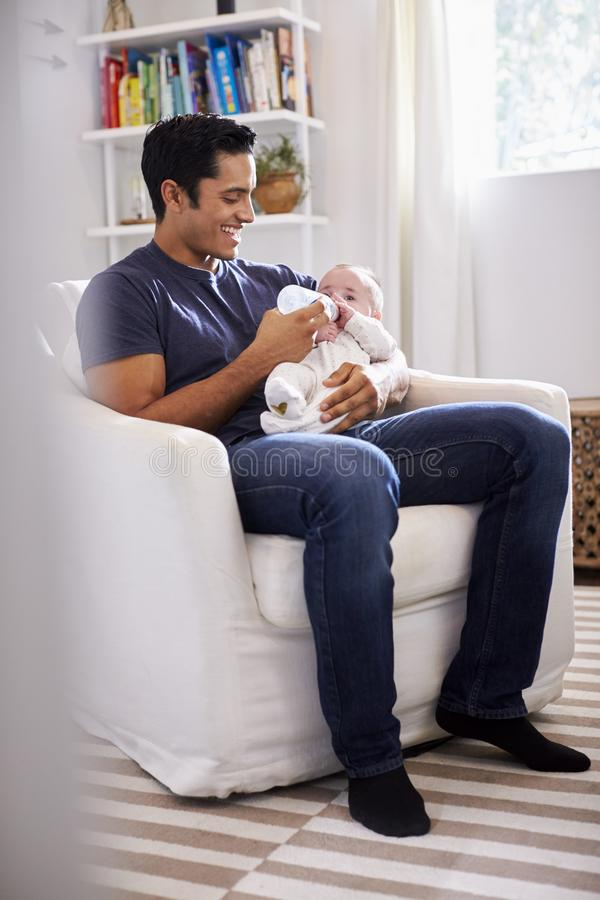 Smiling Hispanic father holding his four month old son feeds him a bottle, full length, vertical stock photos