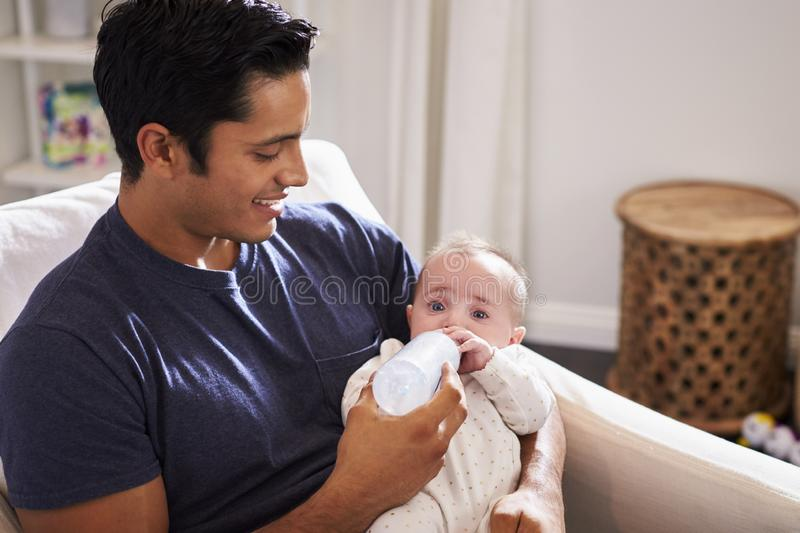 Smiling Hispanic father holding his four month old son feeds him a bottle at home, close up royalty free stock photos