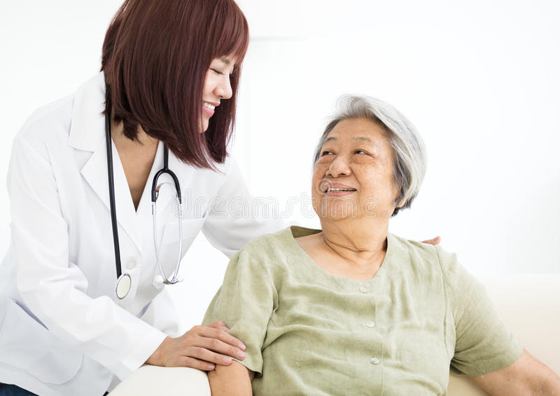 Smiling home caregiver with senior woman. Young smiling home caregiver with senior woman stock image