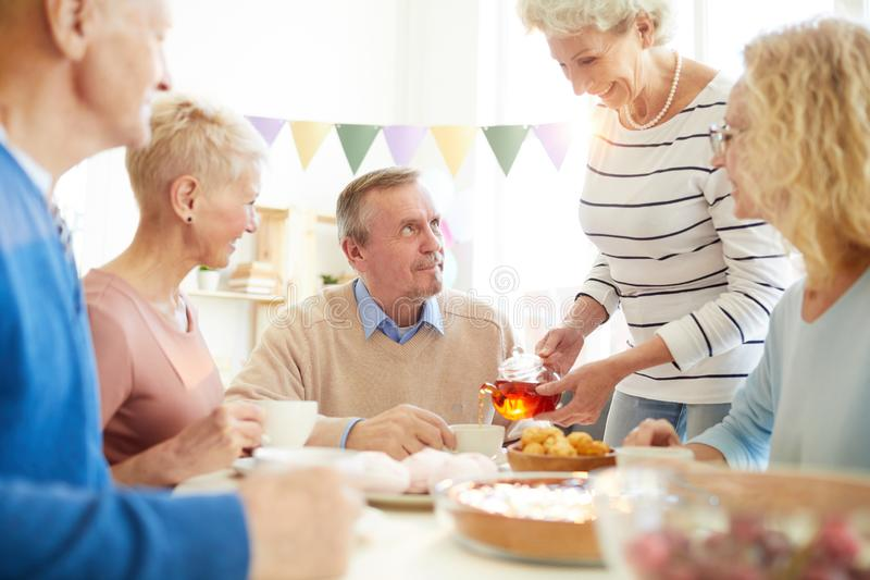 Hospitable lady pouring tea to friends royalty free stock photos