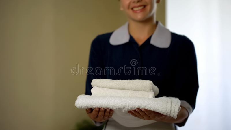 Smiling hotel worker showing clean pillows, good housekeeping, health standard stock photo