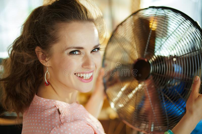 Smiling housewife enjoying breeze air in front of working fan. Portrait of smiling modern housewife in the modern living room in sunny hot summer day enjoying stock image