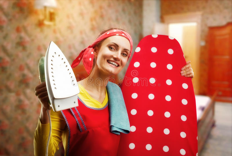 Smiling housewife with ironing-board and iron. Happy smiling housewife with ironing-board and iron stock photography
