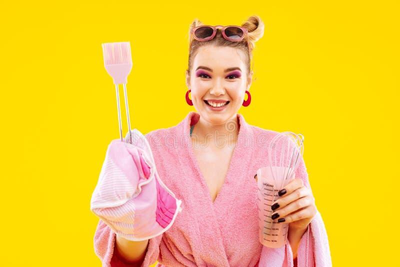 Smiling housewife with pink eye shades holding potholder royalty free stock image