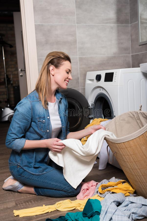 smiling housewife taking clothing to put it into washing machine stock photography
