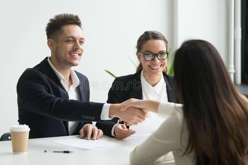 Smiling hr manager handshaking hired female applicant at job int. Smiling hr manager and hired female applicant won job interview shaking hands, friendly stock photography